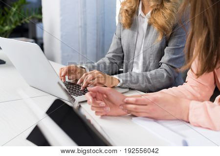 Businesswomen Use Laptop Computer Typing On Keyboard, Teamwork Concept, Open Space Office Two Business Women Working On Project Together Sitting At Desk