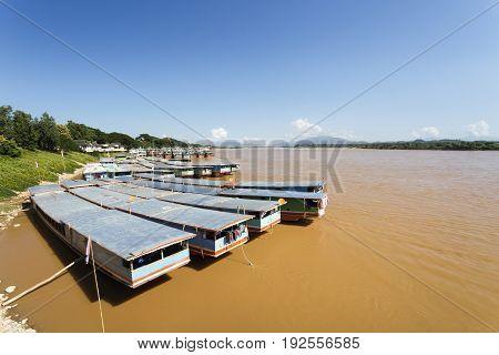 Row of Laos and Chinese cargo boats anchored in Mekong river at berth of Chiang saen ,Chiang rai, Thailand