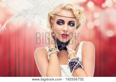 Beautiful retro style young woman with dark make-up and feathers on head over red curtain background. bokeh effect. Copy space.