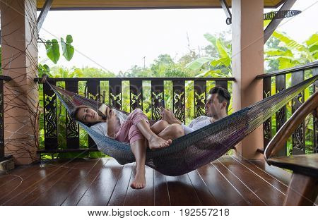 Young Couple Lying In Hammock On Terrace Tropical Hotel, Man And Woman Using Cell Smart Phone Chatting Tropic Holiday Vacation Green Forest
