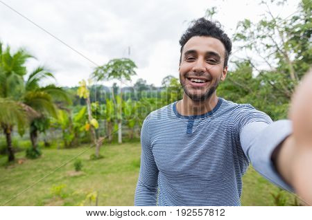 Happy Smiling Latin Man Taking Selfie Photo Over Green Tropical Rain Forest Landscape On Cell Smart Phone