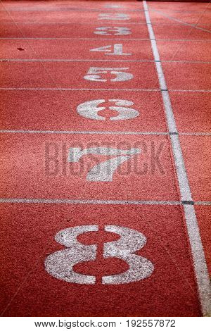 View of a red tartan athletic running track with white numbers