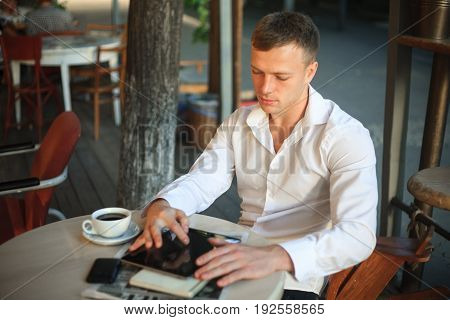 Young man drinking coffee and using digital tablet computer in street cafe.