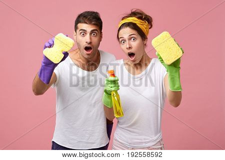 Portrait Of Funny Emotional Young Caucasian Couple In Rubber Gloves Having Astonished And Shocked Fa