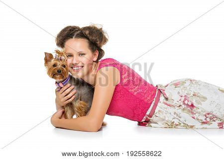 Beautiful young teenage girl in top and skirt holding small cute yorkshire terrier dog. Copy space. Studio shot on light background.