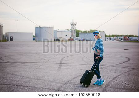 Young Slim Woman Dressed In Blue Checked Shirt Sunglasses, Cap And Jeans, Will Depart At Dawn On Sum