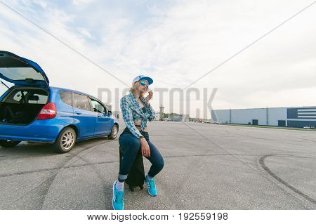 Young Slim Woman Dressed In Blue Checked Shirt, Cap And Jeans, Will Depart At Dawn On Summer Day On