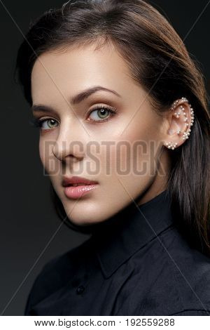 Beautiful young woman with natural make up and pearls glued on ear wearing black shirt. Beauty shot on black background. Copy space.