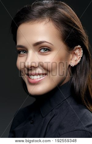 Beautiful young happy woman with natural make up and pearls glued on ear wearing black shirt. Beauty shot on black background. Copy space.
