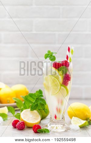 Lemon mojito cocktail with lime, mint and raspberry, cold drink with ice.