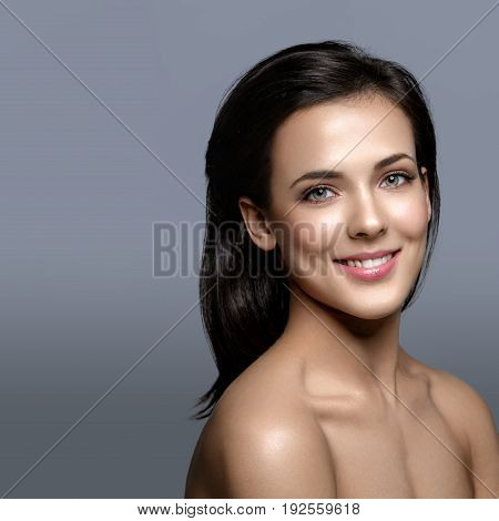 Beautiful happy young woman with healthy glowing skin and natural makeup. Beauty shot on grey background. Copy space. Square composition.