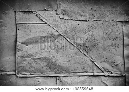 Dark grunge texture: rusty metal surface covered with paint flaking and cracking texture with seams and rivets