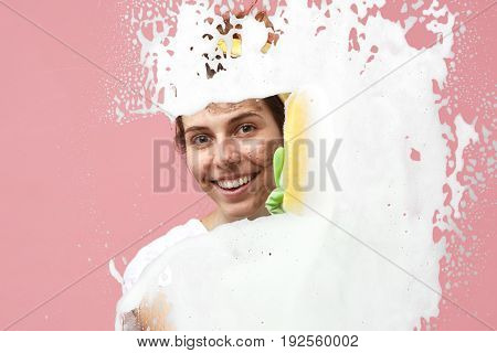 Attractive Smiling Young Caucasian Housewife Doing Her Daily Routine Household Chores, Washing Windo