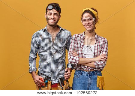 Indoor Portrait Of Positive Cute Young Couple Of Professional Maintenance Workers Wearing Overalls A