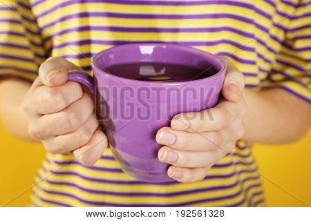 Woman holding beautiful lilac color cup, closeup