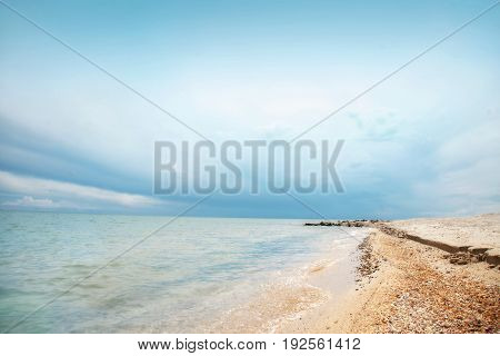 Beach of the sea coast with clean sand on a clear day with a blue sky.