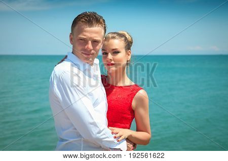 Man is hugging a woman delicatly posing with her by the sea. Portrait of a beautiful couple on vacation.