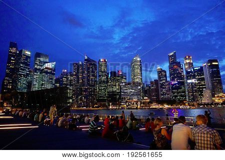 Singapore, Singapore - February 14, 2017: People watch the Marina Bay Sands laser show in the Waterfront by night in Singapore.