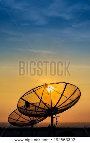 Satellite dish communication technology network silhouette (black shadow) on building rooftop with yellow gold sunset and blue sky background in urban or city area