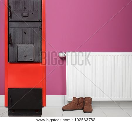 Energy savings concept. Solid fuel boiler and radiator with shoes on color wall background
