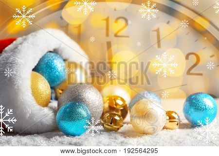 Countdown to holiday celebration. Christmas decorations with Santa hat and clock on background