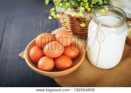Fresh chicken eggs and a jar with milk on the kitchen table. Still life with farm products.