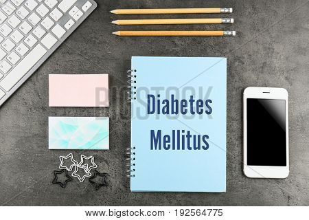 Health care concept. Notebook with title DIABETES MELLITUS, phone and stationery on gray background