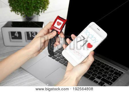 Woman holding heart rate monitor watch and smart phone at table
