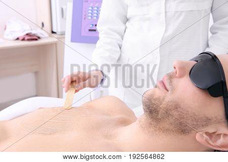 Handsome man getting laser epilation in beauty salon