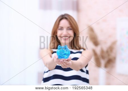 Happy young woman holding piggy bank at home