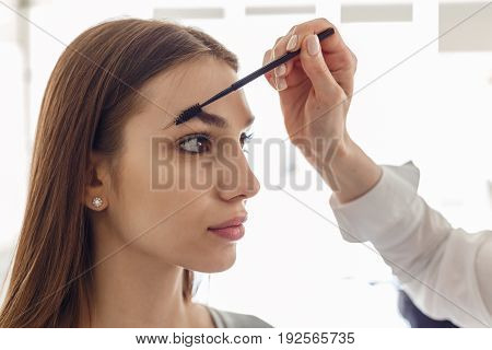 Portrait of a beautiful model during an eyebrow correction procedure. Woman correcting eyebrows form