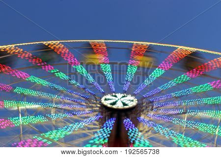 colorful giant wheel in motion at sunset at the fair