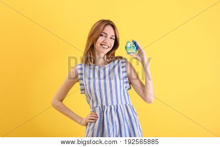 Happy young woman holding piggy bank on color background