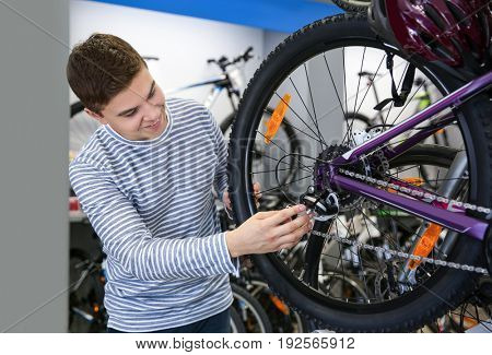 Smiling boy checking bicycles in shop