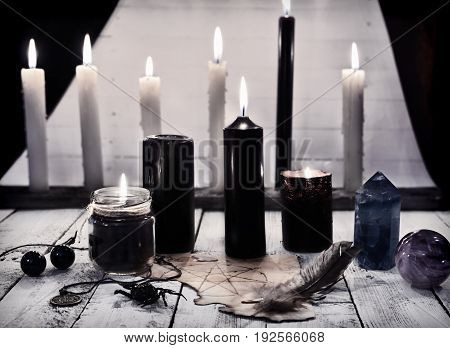 Mystic still life with black candles and pentagram on paper. Halloween concept. Mystic background with occult and magic objects on witch table