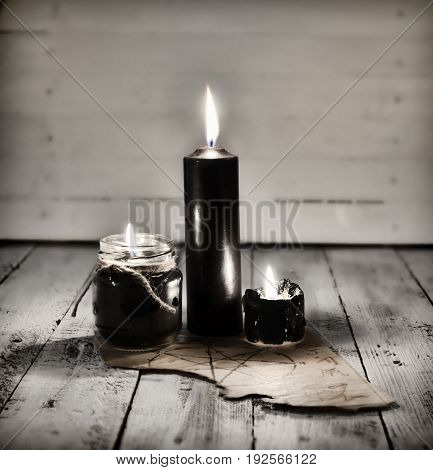 Three black candles and old manuscript with pentagram on wooden table. Halloween concept. Mystic background with occult and magic objects on witch table