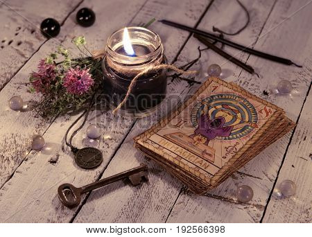 Black candle and old tarot cards on wooden planks. Halloween and fortune telling concept. Mystic background with occult and magic objects on witch table
