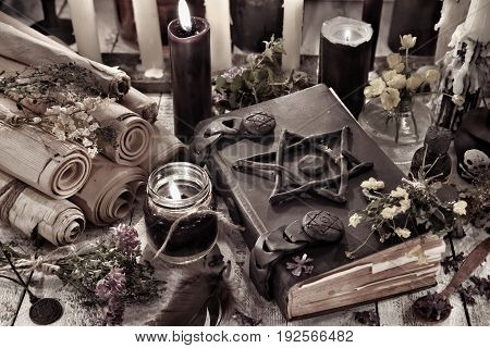 Black magic book with burning candles and ancient scrolls. Halloween concept. Mystic background with occult and magic objects on witch table