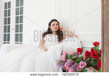 bride in a wedding dress and a Crown sits in the White Hall at the wedding