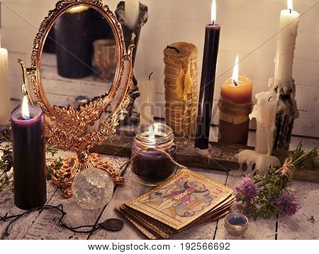 Fortune telling still life with the tarot cards, mirror and burning candles. Halloween concept. Mystic background with occult and magic objects on witch table