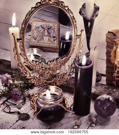 Toned still life with magic mirror and reflection of the tarot card. Fortune telling and halloween concept. Mystic background with occult and magic objects on witch table