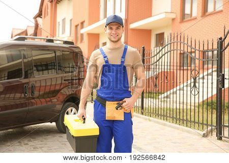 Young smiling electrician with toolbox outdoors