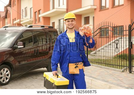 Young smiling electrician with bunch of wires and toolbox outdoors