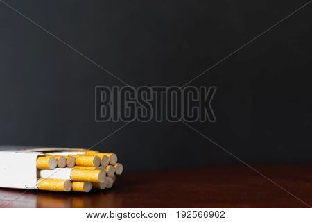 Pack of cigarettes on the table mahogany. Dark background