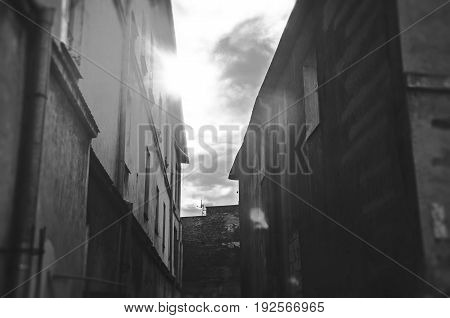 sunlight between tenement buildings in old town black and white dreamy version