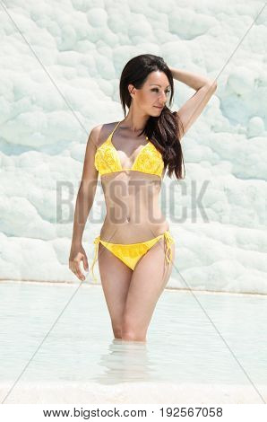 Beautiful brunette girl in yellow swimsuit in pamukkale. This is a natural site in the province of Denizli in the south-west of Turkey
