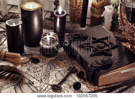 Toned still life with black magic book, demon paper and black candles. Halloween concept. Mystic background with occult and magic objects on witch table