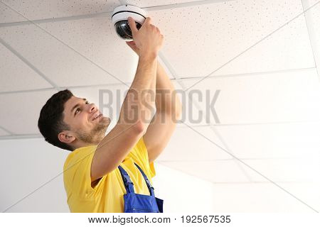 Electrician fixing video surveillance camera indoors