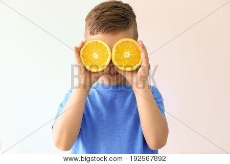 Cute little boy with halves of orange on light background
