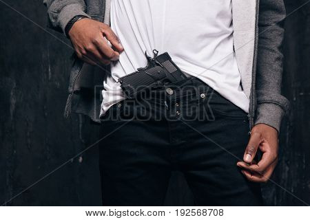 Unrecognizable black man threatens with a gun closeup studio shoot. Ghetto gangster with weapon on dark background. Outlaw, ghetto, murderer, robbery concept